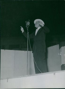 Maurice Auguste Chevalier standing on stage.