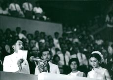 A prominent man giving speech, inside the auditorium, on a podium, holding a piece of paper, 1967.