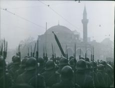 Bulgarian soldiers gathered in street, view of a mosque in the background.