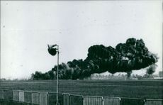 Huge black smoke coming from a blast, spreading through the field.
