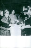 A lady holding the box of ballot for the other women to put on their papers.