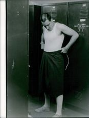 Man standing getting ready in the lockers room.