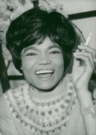Eartha Kitt with a cigarette in his hand, laughing