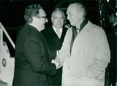 Henry Kissinger is greeted by British Foreign Minister Alec Douglas-Home on arrival at Heathrow Airport