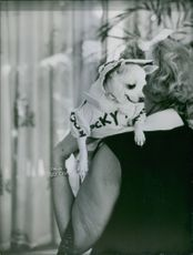A lady related to Nelson Rockefeller, holding a dog on his shoulder.
