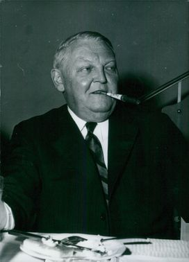 Photo showing West German Politician, Dr. Ludwig Erhard smoking a cigarette after having a meal.