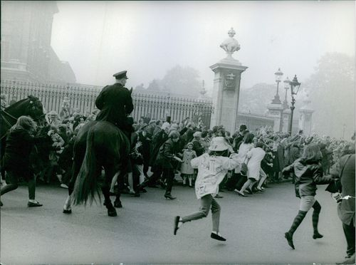 People gathered in street and running towards the members of the Beatles in 1965.