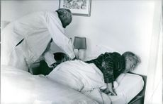 An old man being examined by a physician.