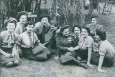 Women sitting on the ground and smiling for the camera.