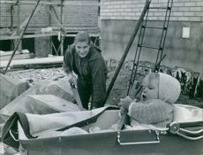 Woman cutting wood with saw and looking towards her child in pram.
