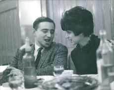 A man and a woman sitting on dining table and talking to each other.