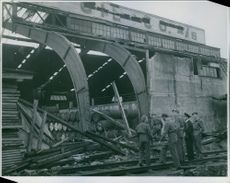 Soldiers standing and looking a destroyed warehouse due to Sabotage.