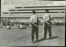 Armed guards watch the Italian gymnastics team while they warm up - the Olympic Games in Montreal in 1976