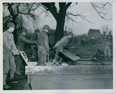 U.S. soldiers build homes for bombed-out London war workers.