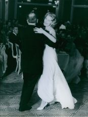 American actress Rhonda Fleming is dancing with a men in a party