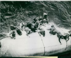 Passengers of the capsized Smith Voyager as their rescue boat flipped upside down and they try to climb its hull to save their lives.  Taken - 1965