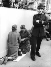 Two women of unknown personality  kneeling on the side of the road with royal guard laughing because of what they are about to do.