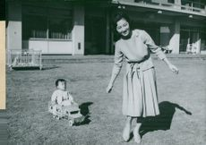 Prince Hiro is drawn by his mother, Princess Michiko is sitting in her toy car in the garden