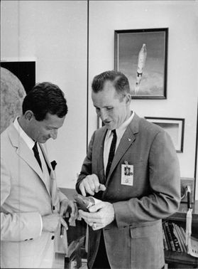 Ed White and man looking at model of rocket.