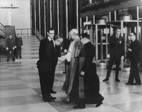 Pope Paul VI shaking hands with people.