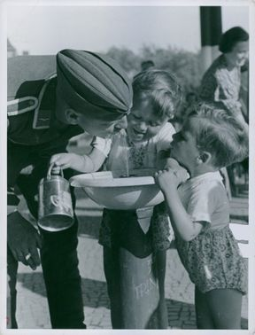 A soldier drinking at the water fountain with two young children.
