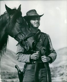 David Ladd holding horse by the bridle.