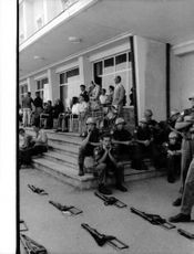 A group of military officers sitting on the stairs.
