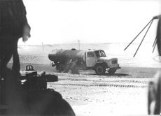 A soldier aiming his gun and looking at a parked truck on the road.