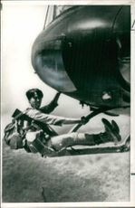 A South Vietnamese soldier hanging on American helicopter