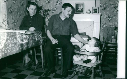 Man playing with child, woman looking at them.