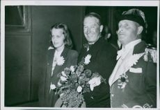 Maurice Auguste Chevalier with a girl and a man, holding a bouquet in hand.