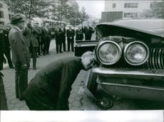 Man inspecting a Smuggling car. 1963