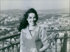 Jacqueline Boyer standing on terrace and smiling, 1960