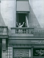 Elsa Maxwell standing at the balcony raising her two hands in Paris, 1960.