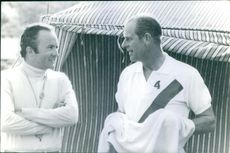 Prince Philip standing and talking to man.