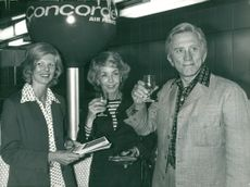 Kirk Douglas with wife Anne Buydens receives a welcome drink at Air France Concorde