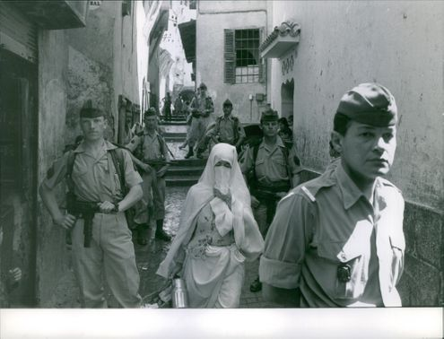 Soldiers standing on a passage way with a Muslim woman passing by, during the war in Algeria, 1961.
