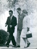 Juan Domingo Perón talking with a man and a lady while walking.
