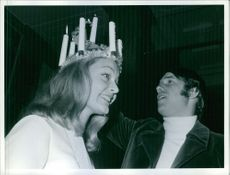 Man lighting candles in Lucia crown of Kerstin Asp, 1968.