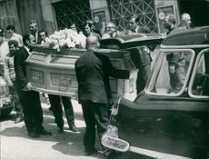 A photo of a wife of Stavros Niarchos wife Eugenia Livanos coffin being lifted by men to transfer in a coffin carrier during her funeral.