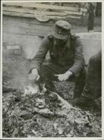 To protect against the damp November cold, the prisoners raise fire directly on the ground. 1944.