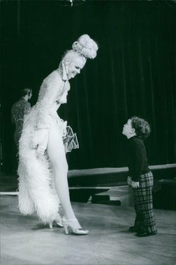 A female performer smiles as the young boy looked curiously at her.