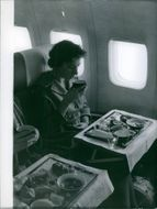 A woman inside of airplane having a tea in Atlantic, 1959.