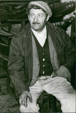 Vintage photo of a man sitting on a chair, his hand holding a cigarette and resting on his knees, his left hand in his pocket.