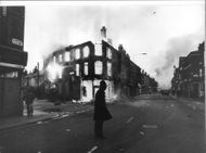 A lone policeman is guarded in front of a burning building after the riots in Toxteth