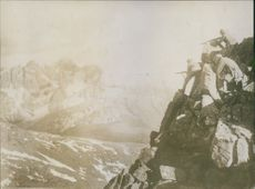 Soldiers standing at the cliff of a mountain and firing during World War I, 1935.
