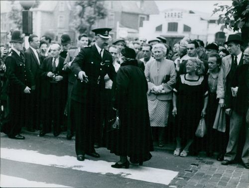 A police officer assisting an old woman in-front of the crowd of people.