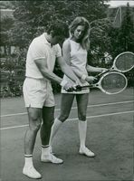 Pierre Barthes teaching his wife Carylou Dale Harris tennis.