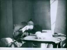 A photo of a  French general who reached the distinction of Marshal of France, and was later Chief of State of Vichy France Philippe Petain drinking tea in a room.