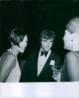 English actor and singer Anthony Newley seen with his wife actress Joan Collins in a party, while Joan is talking with a lady and Anthony looking at something
